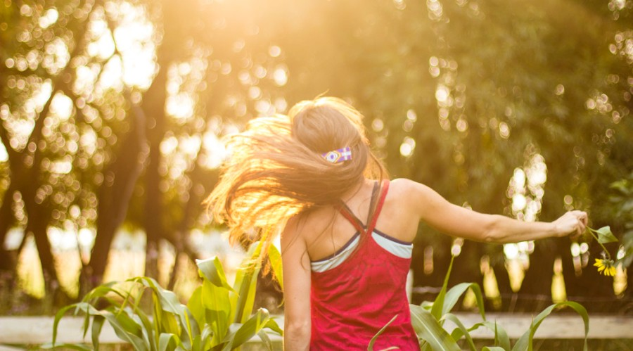 Woman flips her hair in a carefree manner in her summer garden in Montana